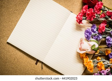 Book and flowers on wooden table