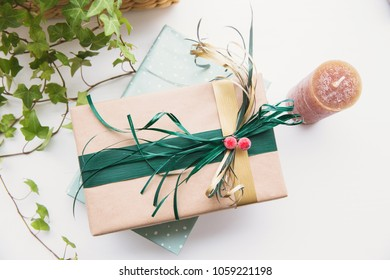 Book and gift box with ribbon decoration on the table. Christmas or holiday gift, ivy plant and brown candle