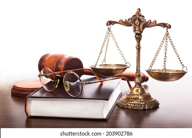 Book, glasses, antique scales, judges gavel on the table