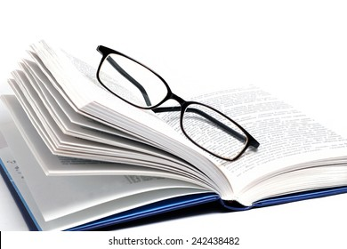 book and glasses isolated on white background