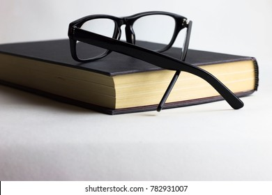 A book and glasses on white background