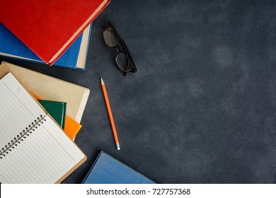 Book glasses and pencil on the desk with study and education concept