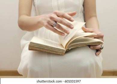 book in the hands of a girl close-up, girl in a white dress, girl holding book in hands with love to reading. Close up of female hands and book.