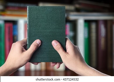 The book is in the hands of man in the library. First-person view