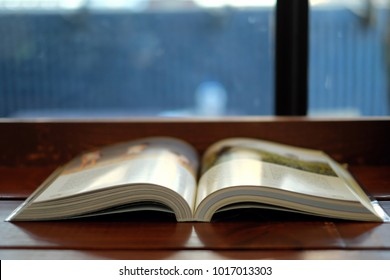 A book has Thai alphabet and two blur images.It was opened on wooden bar that page was separated two side.The background is glass window that It has stain.
