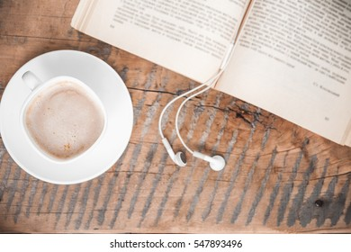 Book, headphones and cup of coffee, read audiobook