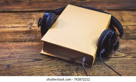 book and headphones on a wooden background. concept of audiobook.