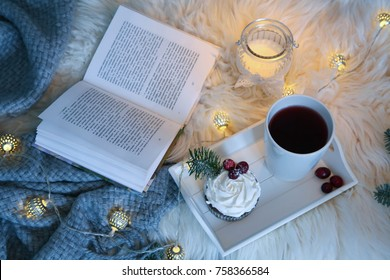 book and hot tea on bed