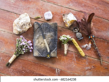 Book of incantations, grimoire, dried flowers, thistle, wand of feathers, quartzite crystal and candles made from natural wax, witchcraft, spells, magic, Wicca, goddess