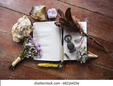 Book of incantations, grimoire, dried flowers, thistle, wand of feathers, quartzite crystal and candles made from natural wax, witchcraft, spells, magic, wicca, center for text, goddess