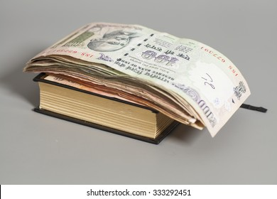 Book with Indian Currency Rupee bank notes on gray background