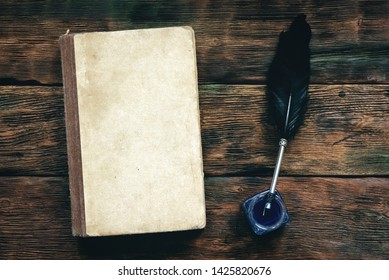 Book, inkwell and a quill pen on a wooden table background with copy space.