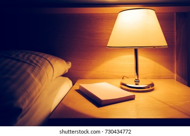 Book and lamp on night table in hotel room next to the empty bed and pillow