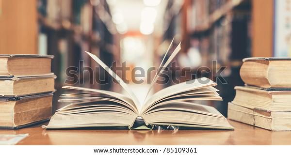 Buch in der Bibliothek mit alten offenen Lehrbüchern, Stapel von Literatur-Textarchiv auf dem Lesesessel und Gang der Bücherregale im Schulstudienraum für akademisches Lernkonzept