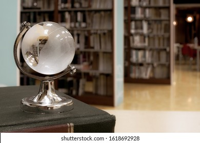 Book in library with small crystal globe at the top. Traditional education learning by studying in library with blurred background of aisle of bookshelves. For education learning concept. Copy space.
