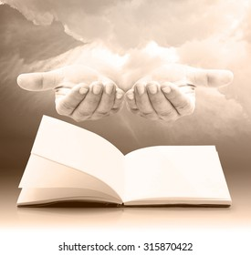 Book of life concept: Human open empty hand with palms up with empty book over amazing sky background.
