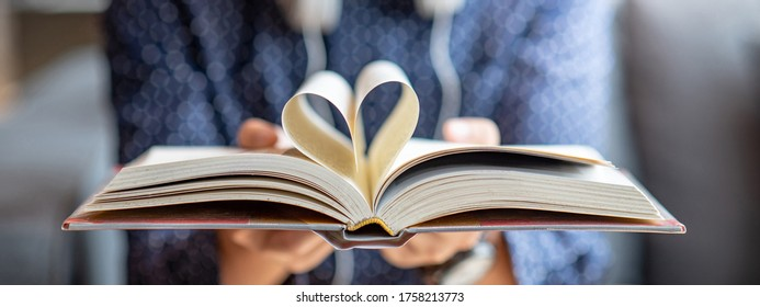 Book lover or love reading concepts. Male hand holding book with heart shape page folded.