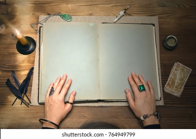 Book of magic with copy space. Tarot cards on fortune teller desk table. Future reading. Woman witch reads a ancient magic scroll book and learn art of prediction on wooden table.