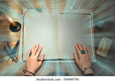 Book of magic with mystical light and copy space. Tarot cards on fortune teller desk table. Future reading. Woman witch reads a ancient magic scroll book and learn art of prediction on wooden table.