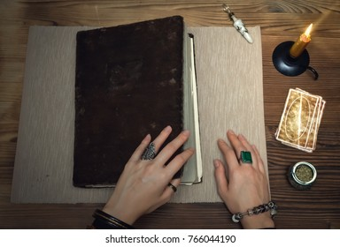 Book of magic with mystical light. Tarot cards on fortune teller desk table. Future reading. Woman witch open ancient magic scroll book and learn art of prediction on wooden table.