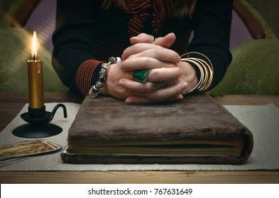 Book of magic. Tarot cards on fortune teller desk table. Future reading. Woman witch reads a ancient magic scroll book and learn art of prediction on wooden table.