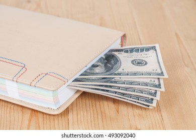 Book with money on wood table with calculator