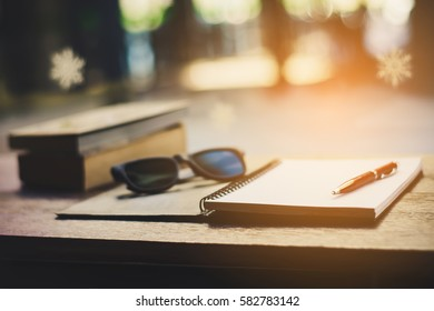 book, note, pens, glasses on the table.