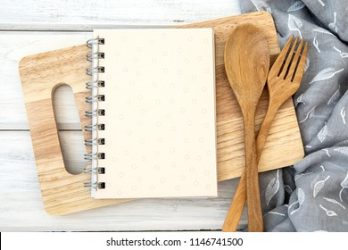 book notepad paper on chopping cutting board and tablecloth on white table , recipes food  for healthy habits shot note background concept