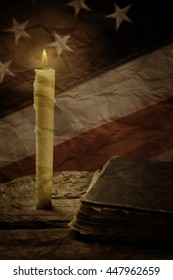 Book and old USA flag. Closed book near burning candle. Pray for good of nation. Silence found in solitude.