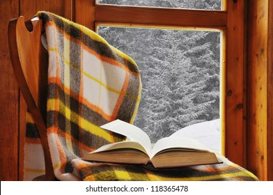 Book on a chair with blanket, in a mountain home with snowfall