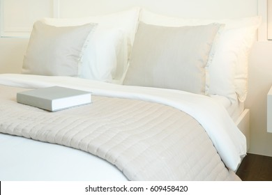 Book on comfy bed in modern bedroom interior