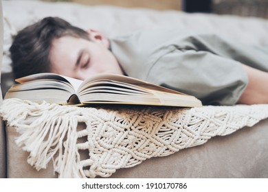 book on couch against blurred background of sleeping young student