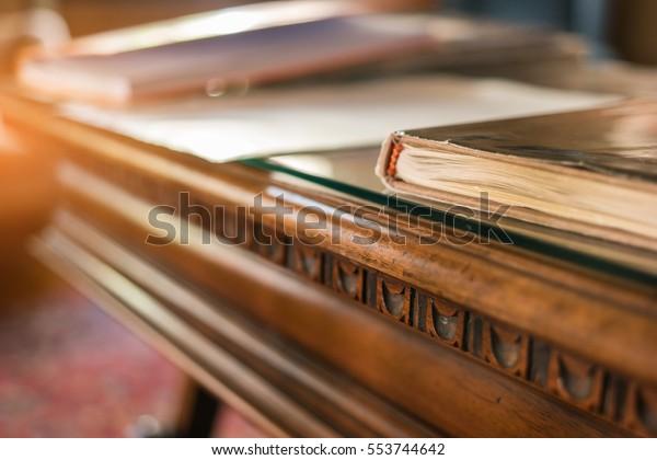 Buchen Sie auf einem alten Holztisch. Schreibtisch und Sonnenlicht. Studieren Sie Geschichte und entdecken Sie Geheimnisse.