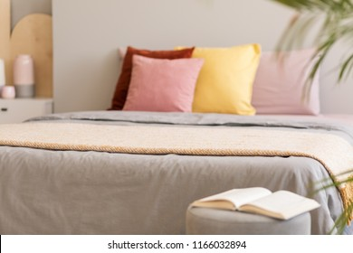 Book on stool next to grey bed with blanket and colorful pillows in bedroom interior. Real photo with focus on the blanket