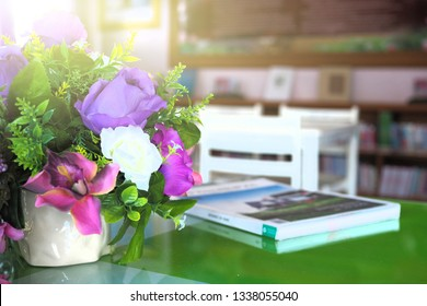 Book is on the table beside the jar of flower in the morning. Many book was disturbed by online content and a few people read paper book nowadays.