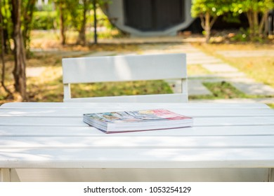 Book on wooden table. They are in a backyard.