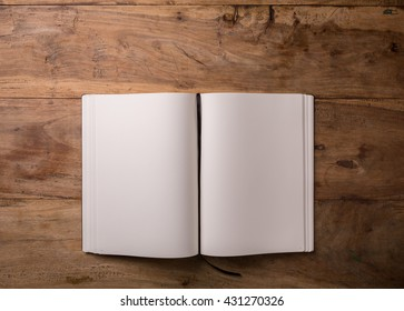 Book opened blank on dark wooden background with copy-space, top-view, closeup.