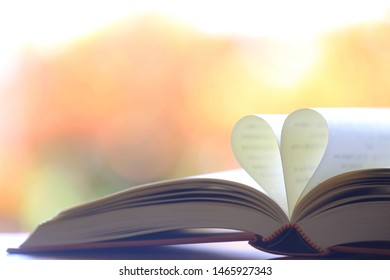 The book opens, and the book page rolls into the heart colorful background selective focus and shallow depth of field