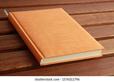 book with orange cover on wooden background