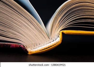 Book pages close up on a dark background. Macro photography in bright colors is suitable as a background on the topics of reading, literature, book business, book publishing.