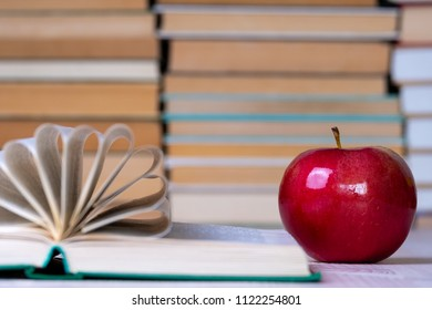 book with the pages curved in a semicircle and a red apple lies on the wooden table, the background is blurred but the books are looked through