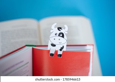 book with paper cow bookmarks , soft focus