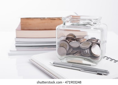 Book, pen with penny jar filled with coins money on white background. education financing concept
