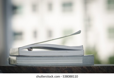 book and pencil between page,building blurred background.
