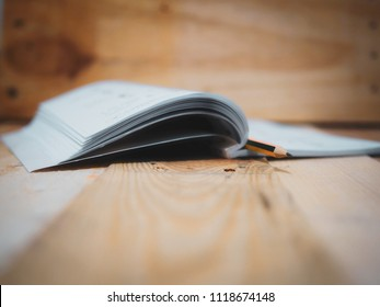 A book with pencil on wooden