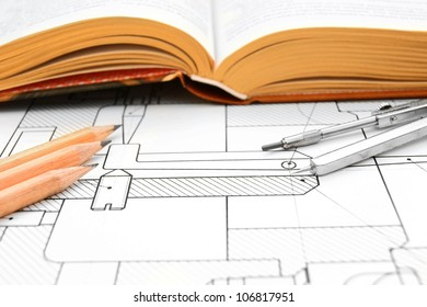 The book, pencils and compasses on the drawing.