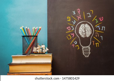 Book, pencils and light bulb with human brain and Hebrew letters on chalkboard