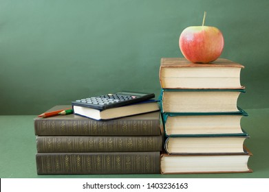 book pile with apple on top on green background, book shelf, back to school concept, teacher's day concept