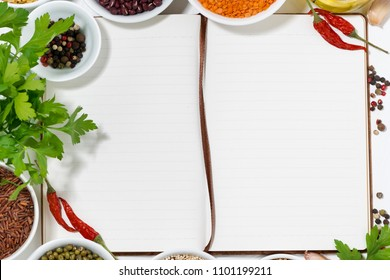 book for recipes, spices and assortment of legumes, closeup top view