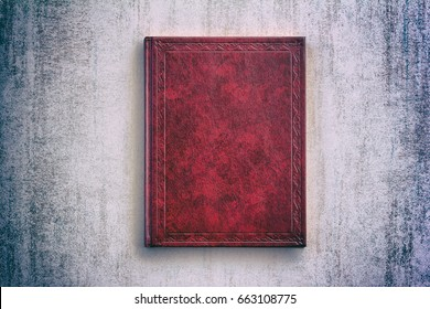 the book in a red cover over gray grunge background, top view with vignette. mock up for the Bible, Koran